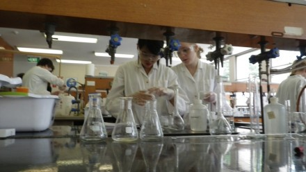 Two chemistry students wearing white labcoats