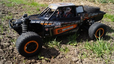 A black remote controlled car in muddy grass
