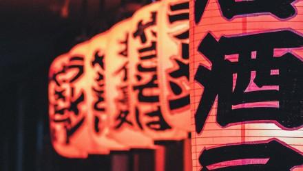 Illuminated paper lanterns with Japanese writing on them at night