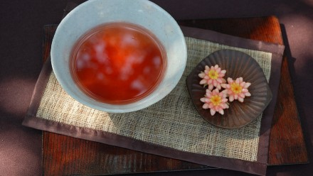 Korean tea in a white bowl with flowers nearby on a mat